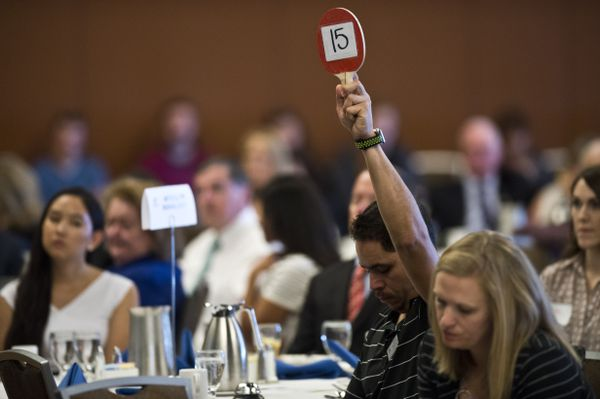 A timekeeper holds up a 15-second warning. Four candidates for governor participated in a lunchtime forum hosted by the Anchorage Chamber of Commerce at the Dena'ina Center on September 10, 2018. (Marc Lester / ADN)
