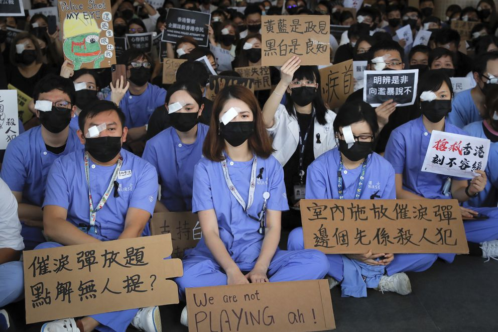 Medical staff stage a protest against police brutality on the protesters, at a hospital in Hong Kong, Tuesday, Aug. 13, 2019. Demonstrators have in recent days focused on their demand for an independent inquiry into what they call the police's abuse of power and negligence. That followed reports and circulating video footage of violent arrests and injuries sustained by protesters. The signs read 'Why no one mentions about tear gas?, ' bottom left and 'Using tear gas at indoor, who is the actual murderer, ' bottom right. (AP Photo/Kin Cheung)