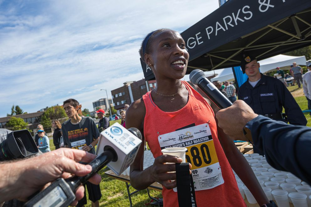 Caroline Kurgat talks with the media after breaking the half marathon record by more than five minutes. (Loren Holmes / ADN)