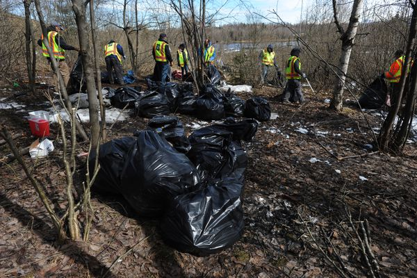 Municipal Parks & Recreation maintenance workers filled garbage bags full of debris that they removed from an abandoned homeless camp nestled between the Hillcrest Drive offramp and Minnesota Drive on Thursday, April 25, 2019. (Bill Roth / ADN)