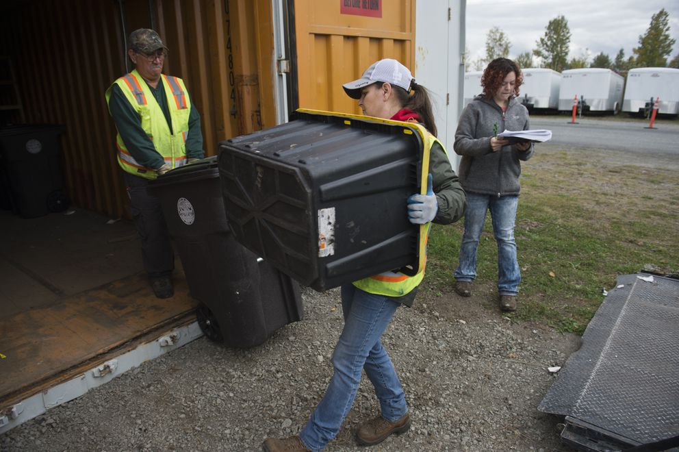 Parks and Recreation employees Manny Garcia and Nicole Limberg load belongings from a homeless camp into a cargo container at the Central Transfer Station on September 21, 2018. Anchorage Community Resource coordinator Rosa Salazar is at right.   (Marc Lester / ADN)