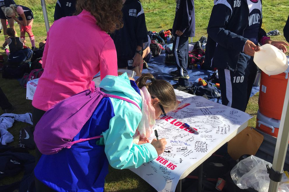A young fan signs a banner in honor of Kikkan Randall during the Big 8 XC Classic cross-country races on Saturday at Kincaid Park. (Matt Tunseth/ADN)