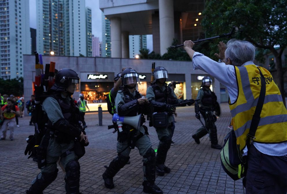 An elderly man tries to block policemen who arrive to arrest protesters at Tung Chung near airport in Hong Kong, Sunday, Sept.1, 2019. Train service to Hong Kong's airport was suspended Sunday as pro-democracy demonstrators gathered there, while protesters outside the British Consulate called on London to grant citizenship to people born in the former colony before its return to China. (AP Photo/Vincent Yu)