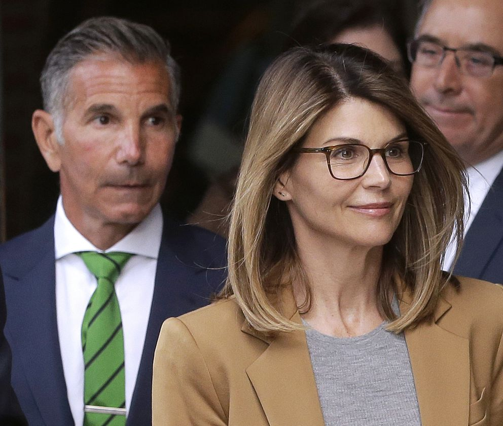 Actress Lori Loughlin, front, and husband Mossimo Giannulli, left, depart federal court in Boston on April 3. (AP Photo/Steven Senne, File)
