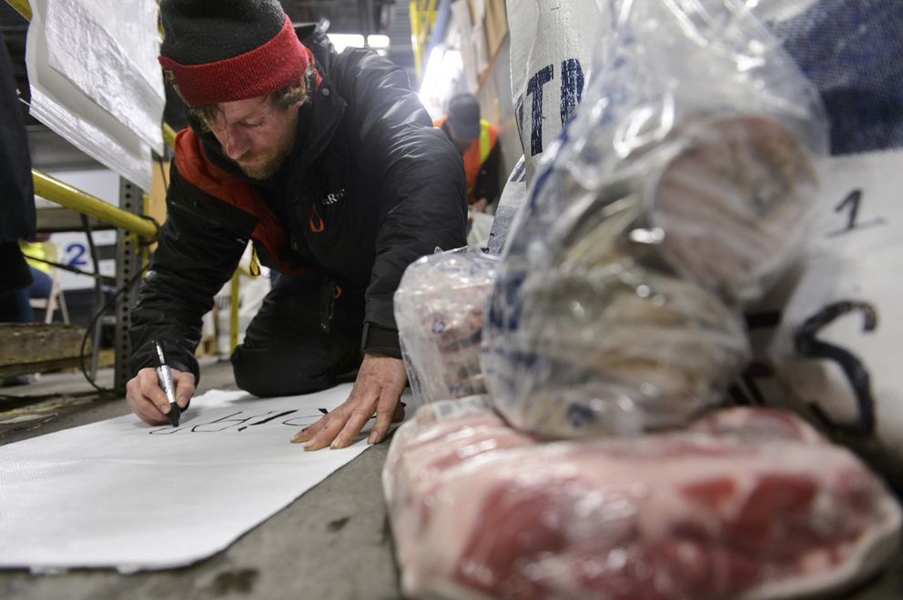 Musher Jessie Holmes, who lives on the Denali Highway, repacks a drop bag that weighed in too heavy. Holmes is preparing to run his third Iditarod. (Marc Lester / ADN)
