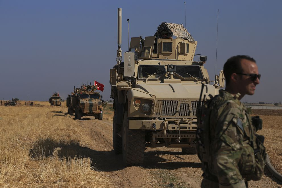 FILE - This Friday, Oct. 4, 2019 file photo, Turkish and American armored vehicles patrol as they conduct joint ground patrol in the so-called 'safe zone ' on the Syrian side of the border with Turkey, near the town of Tal Abyad, northeastern Syria. President Donald Trump's announcement that U.S. troops in Syria would step aside to make way for a Turkish military operation against U.S.-allied Syrian Kurdish fighters unleashed a torrent of near unanimous criticism and warnings of immediate and long-term negative consequences. (AP Photo/Baderkhan Ahmad, File)