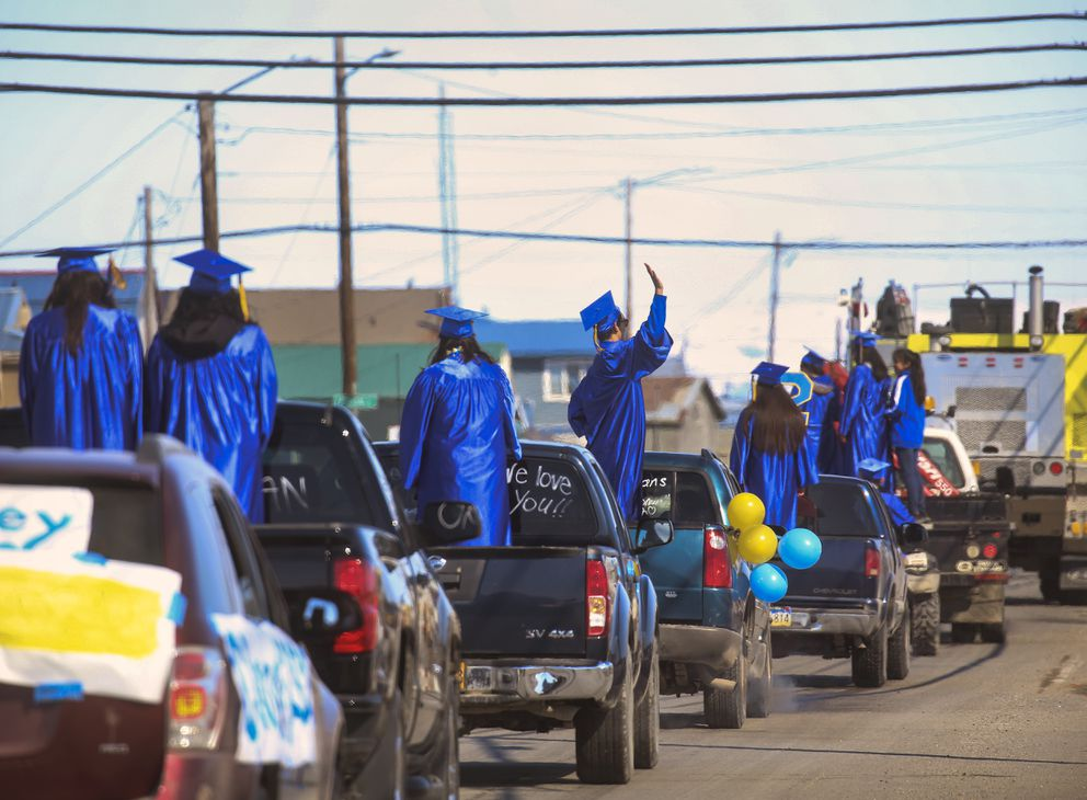 Kotzebue High School seniors stand in the beds of decorated trucks and wave to community members gathered along Third Avenue during a senior graduation parade in Kotzebue on Saturday, May 2, 2020. The parade was created to celebrate and honor the seniors whose graduation ceremony, scheduled for May 2, was cancelled due to social distancing mandates related to COVID-19. (Photo by Emily Mesner)