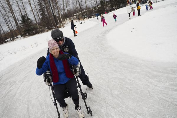 "Ainslie Phillips gets pushed around the ice skating ribbon at Chanshtnu Muldoon Park by Don Wood on Monday, Jan. 15, 2018. Phillips, a former member of the Northeast Community Council, said she's been an advocate of the park, which is nearing the end of its first phase of construction, for twenty years. ""It was my dream back in 1997,"" she said. On Monday, dozens of ice skaters joined many UAA hockey players for a soft opening event to celebrate the park. In a brief game Monday, the Seawolves divided into teams and tried to score at either end of the unique surface, which is C-shaped with loops at either end. Afterward, the public joined them on the ice. Phillips said she remembers when the land, just southeast of the intersection of Debarr Road and Muldoon Road, a place that attracted trash and crime. Phillips said she envisioned a place where kids could connect to being outside. ""This just warms my hear to see my dream come true on Martin Luther King Day,"" she said. (Marc Lester / ADN)"