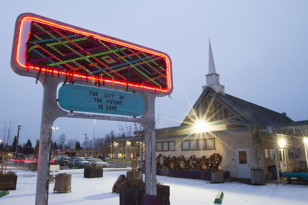 A large sign covered in a textile piece sits outside of the Church of Love in Spenard. (Photo by Philip Hall)