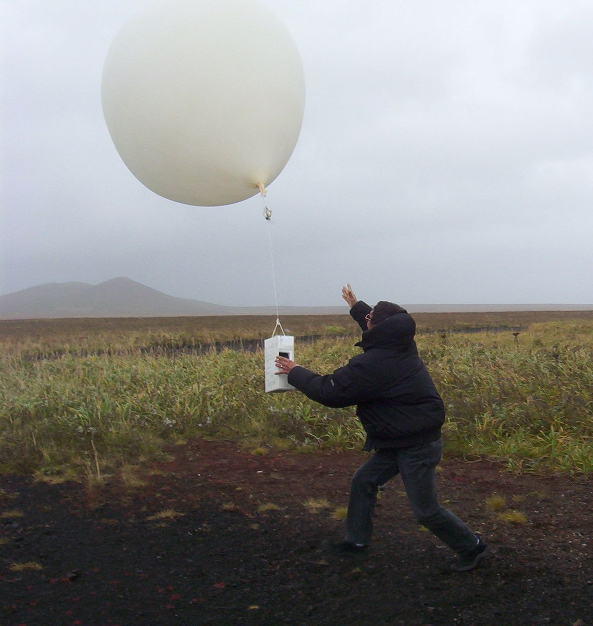 Meteorological technician Willy Tcheripanoff releases a helium-filled weather balloon to gather temperature, humidity, air pressure, wind speed and direction over the Bering Sea in 2004. This balloon rose 110,000 feet before it burst. (Doug O'Harra / ADN archives)