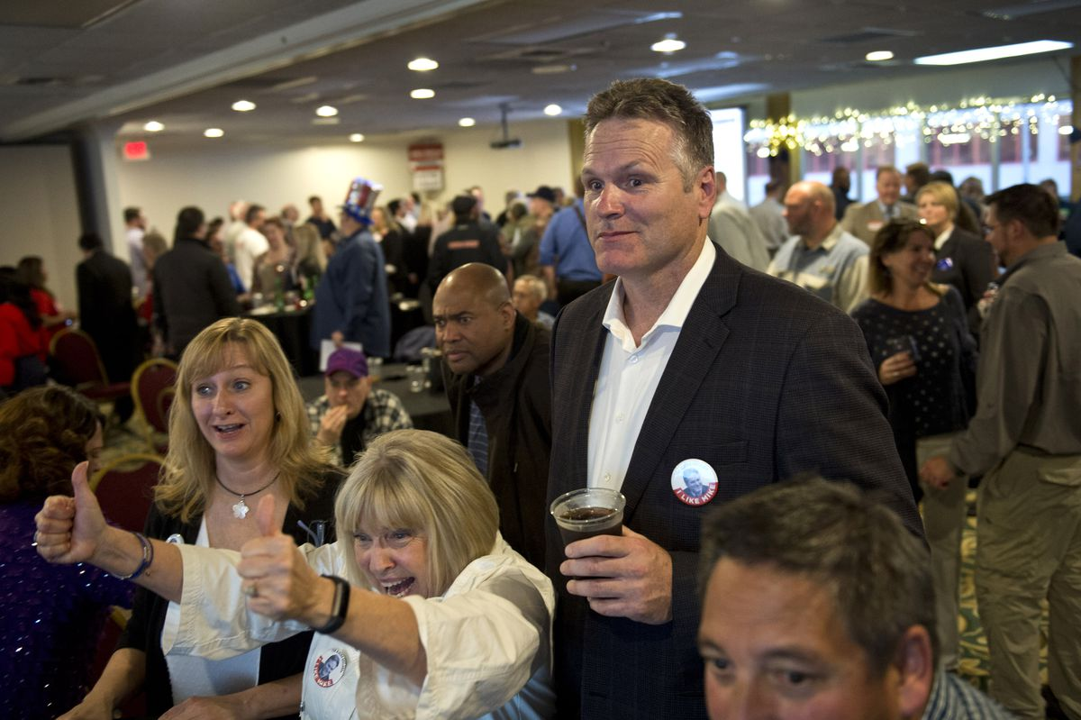 Mike Dunleavy, candidate for governor, watches early results come in at the Aviator Hotel with supporters Bethany Marcum, left, and Judy Eledge on Tuesday. (Marc Lester / ADN)
