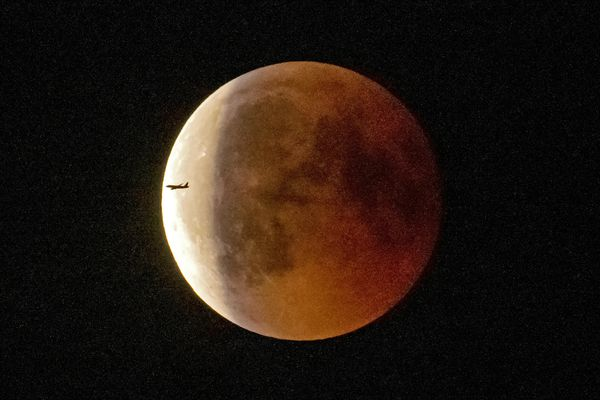An airplane passes the blood moon immediately after the total lunar eclipse in Erfurt, Germany, Friday, July 27, 2018. Skywatchers around much of the world are looking forward to a complete lunar eclipse that will be the longest this century. (AP Photo/Jens Meyer)