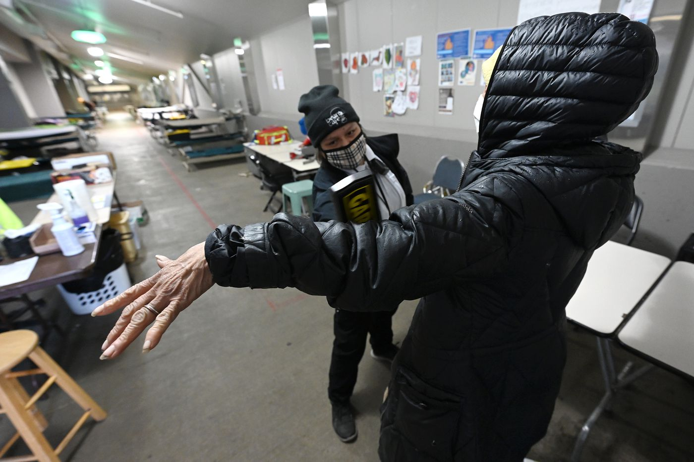 Bean's Cafe safety monitor Lupe Cruz wands a client entering the Mass Emergency Shelter in Sullivan Arena on Feb. 24, 2021. (Bill Roth / ADN)