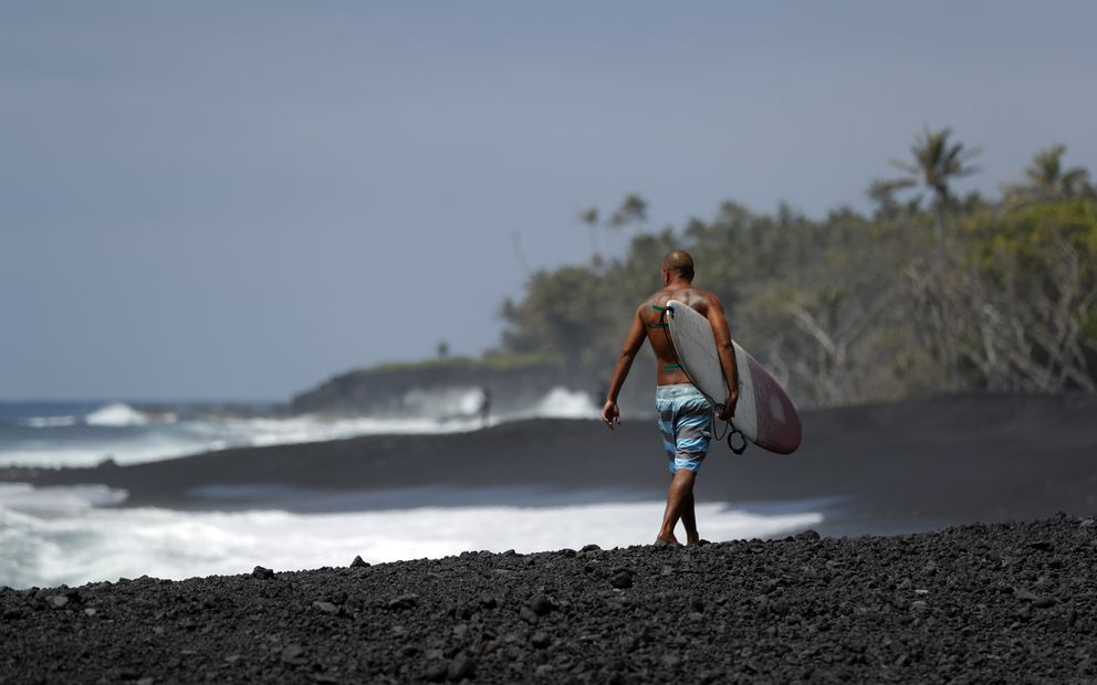 In this Tuesday, April 23, 2019 photo, a surfer walks on a newly formed black sand beach below Kilauea volcano near Kapoho, Hawaii. The beach was created as lava from the 2018 Kilauea eruption entered the ocean, broke apart and churned through the water. Before the eruption, the shoreline was about 100 yards inland from where it is now. (AP Photo/Marco Garcia)