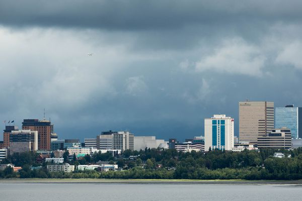 A plane flies over downtown Anchorage Wednesday, Aug. 8, 2018. (Loren Holmes / ADN)