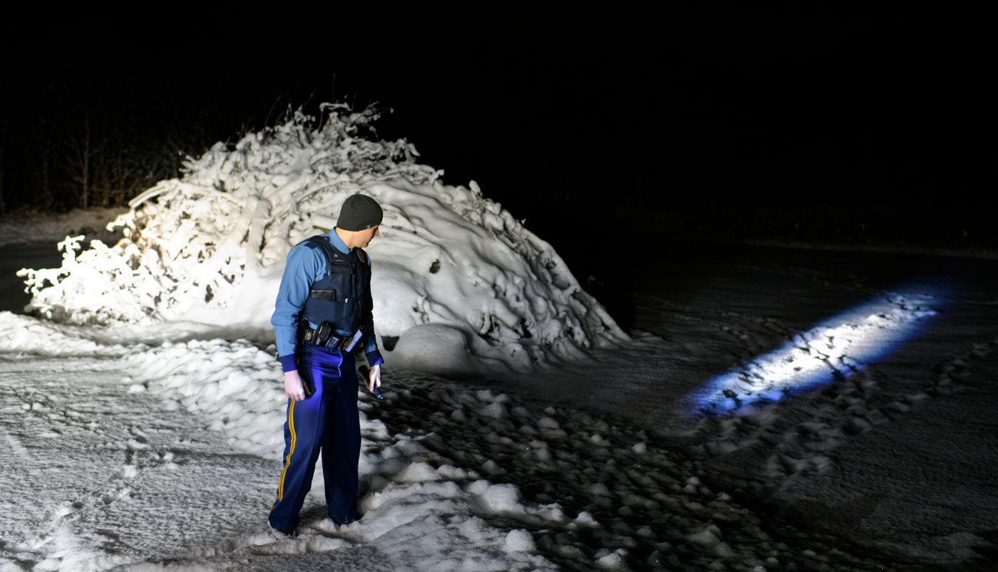 Alaska State Trooper Ryan Anderson looks for new tracks in the snow near a Butte home where a resident reported seeing a suspicious person outside on November 18, 2019. (Marc Lester / ADN)