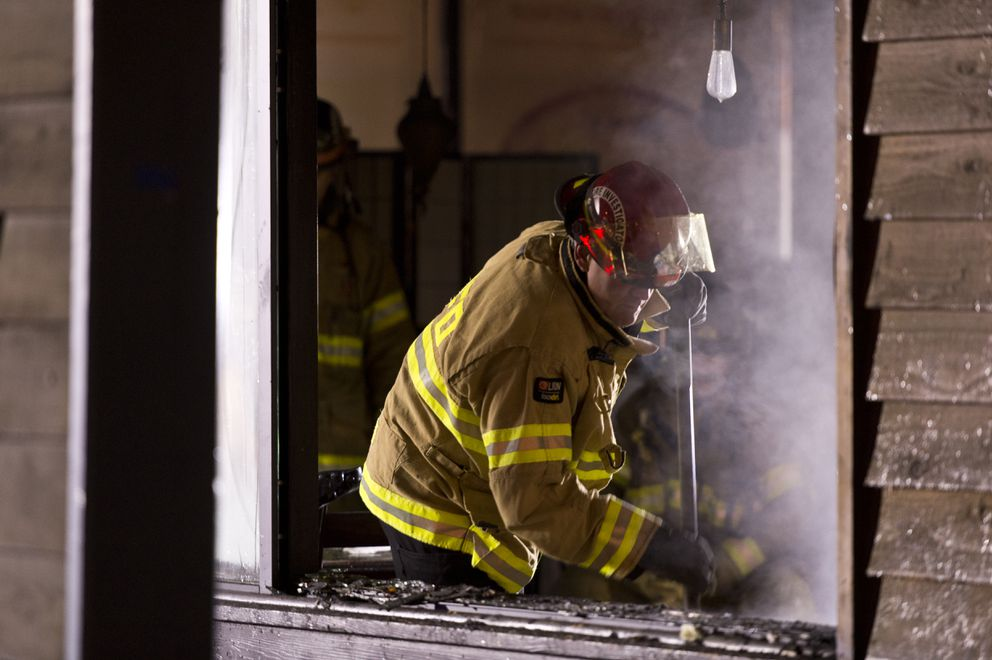 A fire investigator looks through debris after a fire at Noodle World on Tudor Road early Thursday. (Marc Lester / ADN)