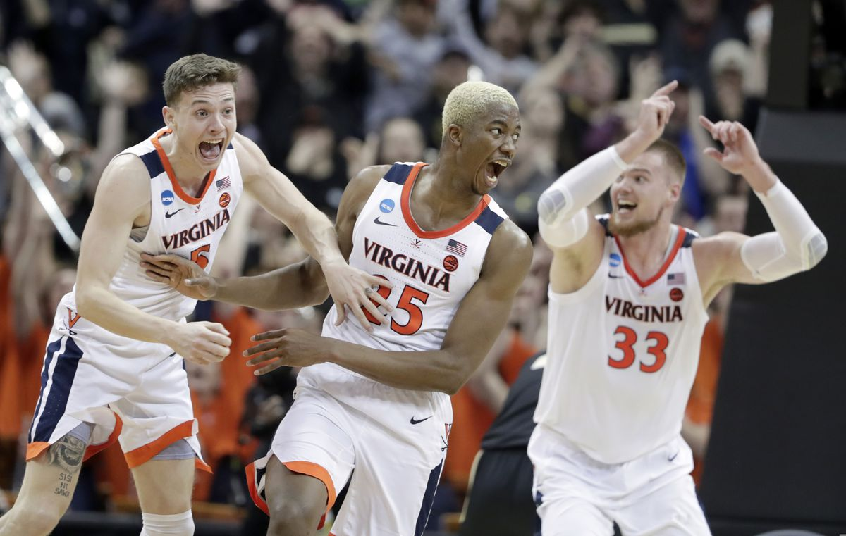 Virginia's Mamadi Diakite, center, reacts with teammates Kyle Guy and Jack Salt (33) after hitting a shot to send the game into overtime in the men's NCAA Tournament college basketball South Regional final game against Purdue, Saturday, March 30, 2019, in Louisville, Ky. (AP Photo/Michael Conroy)