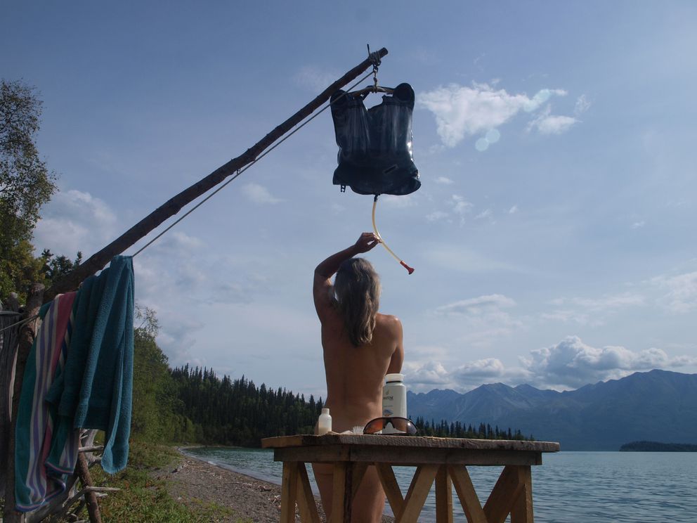 Anne takes a summer shower, courtesy of a black shower bag that's been laid out on the sun-baked beach to warm up. (Steve Kahn)