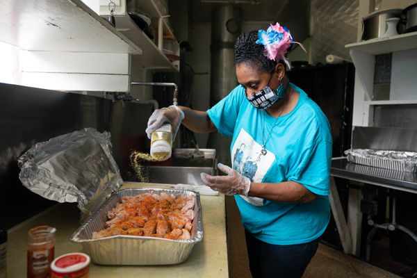 Khanesia Allen of Davons' Place House of Soul seasons chicken at Gathering AK, a guest chef cafe at re:MADE, on Thursday, Aug. 13, 2020 in south Anchorage. (Loren Holmes / ADN)