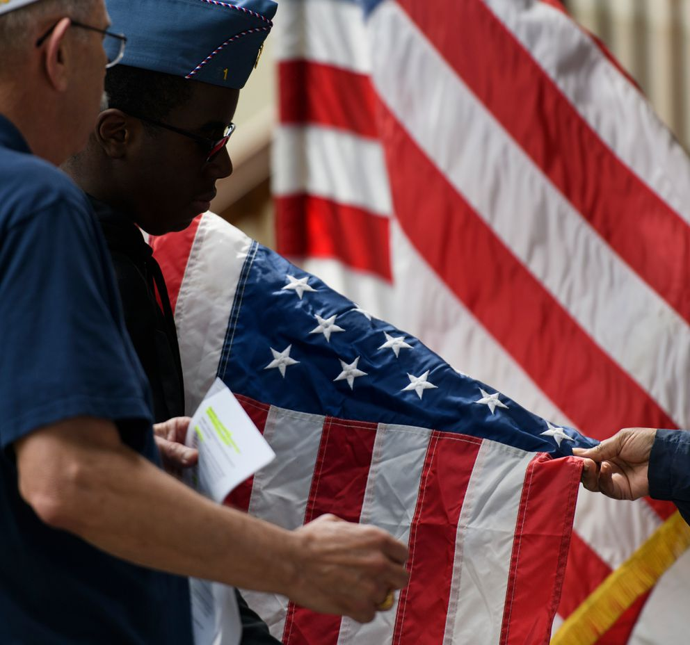 Justin Neal, second from left, holds a U.S. flag for inspection during a flag retirement ceremony. (Marc Lester / ADN)