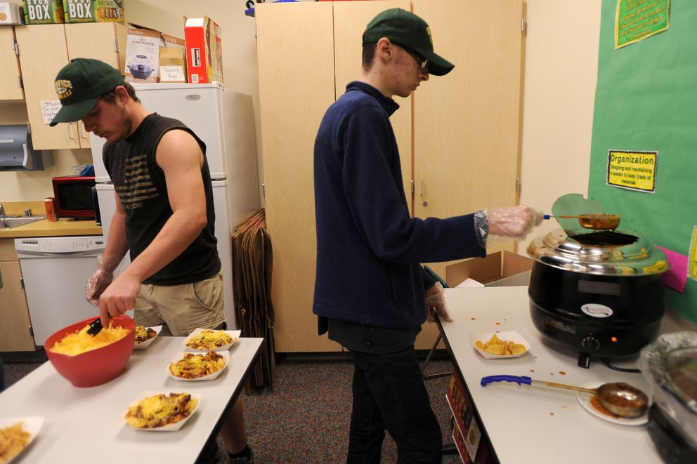 Brandon Godwin, left, and Brian Holthaus prepare Frito pies for sale Friday, Oct. 13, 2017, at Service High School. (Anne Raup / Alaska Dispatch News)