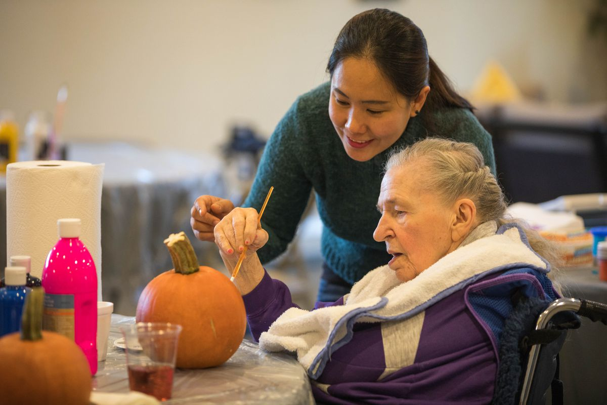 Caregiver Mayzel Tolosa helps client Betty Lee Higgins paint a pumpkin at the Turnagain Social Club on Thursday, Oct. 27, 2016. (Loren Holmes / Alaska Dispatch News)
