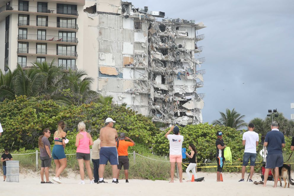 People look at the damage at the 12-story oceanfront Champlain Towers South Condo that collapsed early Thursday, June 24, 2021 in Surfside, Fla.