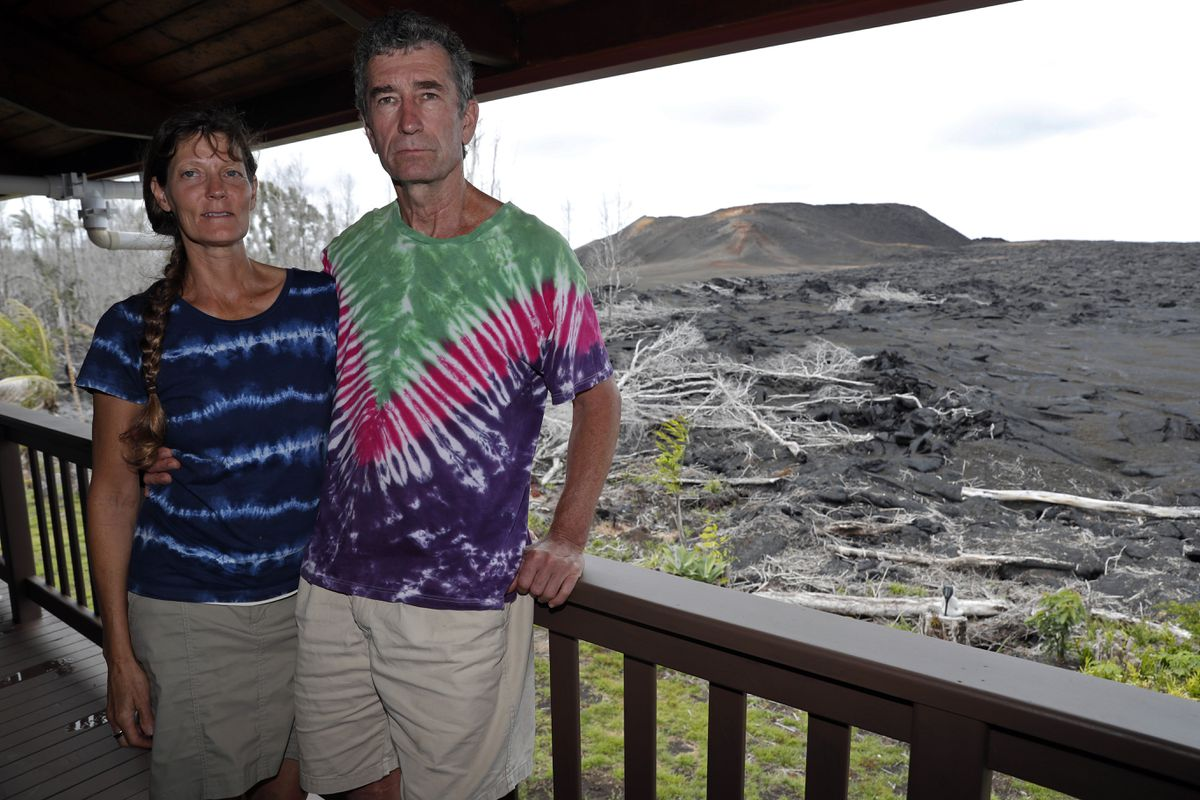 In this Tuesday, April 23, 2019 photo, with a now-dormant towering cinder cone looming in the background, Mark and Jennifer Bishop stand on the deck of their home near Pahoa, Hawaii, which was spared by the lava. The epicenter of the 2018 eruption - one of more than 20 places where the ground split open and released massive explosions of molten rock - is now in their front yard. The red-hot fluid oozed onto their property and stopped about 20 feet from the home. Theirs is now the last house on the street. (AP Photo/Marco Garcia)