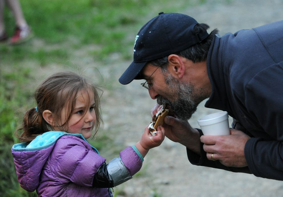 Malina Munro gives her dad Andrew Munro a bite of her s'more.  (Bob Hallinen / ADN)