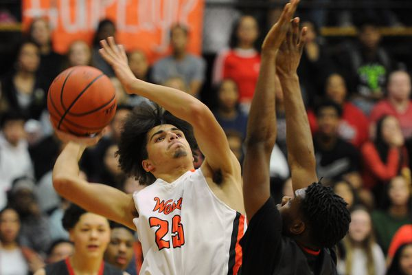 West High senior forward TJ Prater puts up a shot against West Valley defender Chancelor Fields-Colbert during the Wolfpack's 53-51 victory over the Eagles in the Alaska Airlines Classic at West High School on Thursday, Jan. 25, 2018. (Bill Roth / ADN)