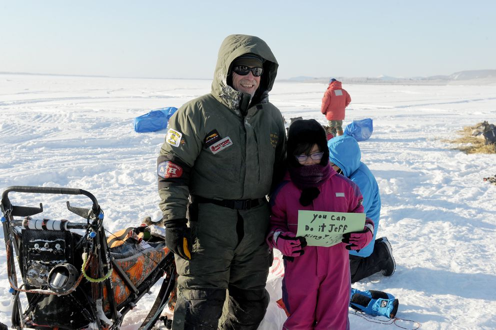 Jeff King poses for a photograph with young fan Cassidy Ekada at the Nulato checkpoint on Sunday. (Bob Hallinen / Alaska Dispatch News)