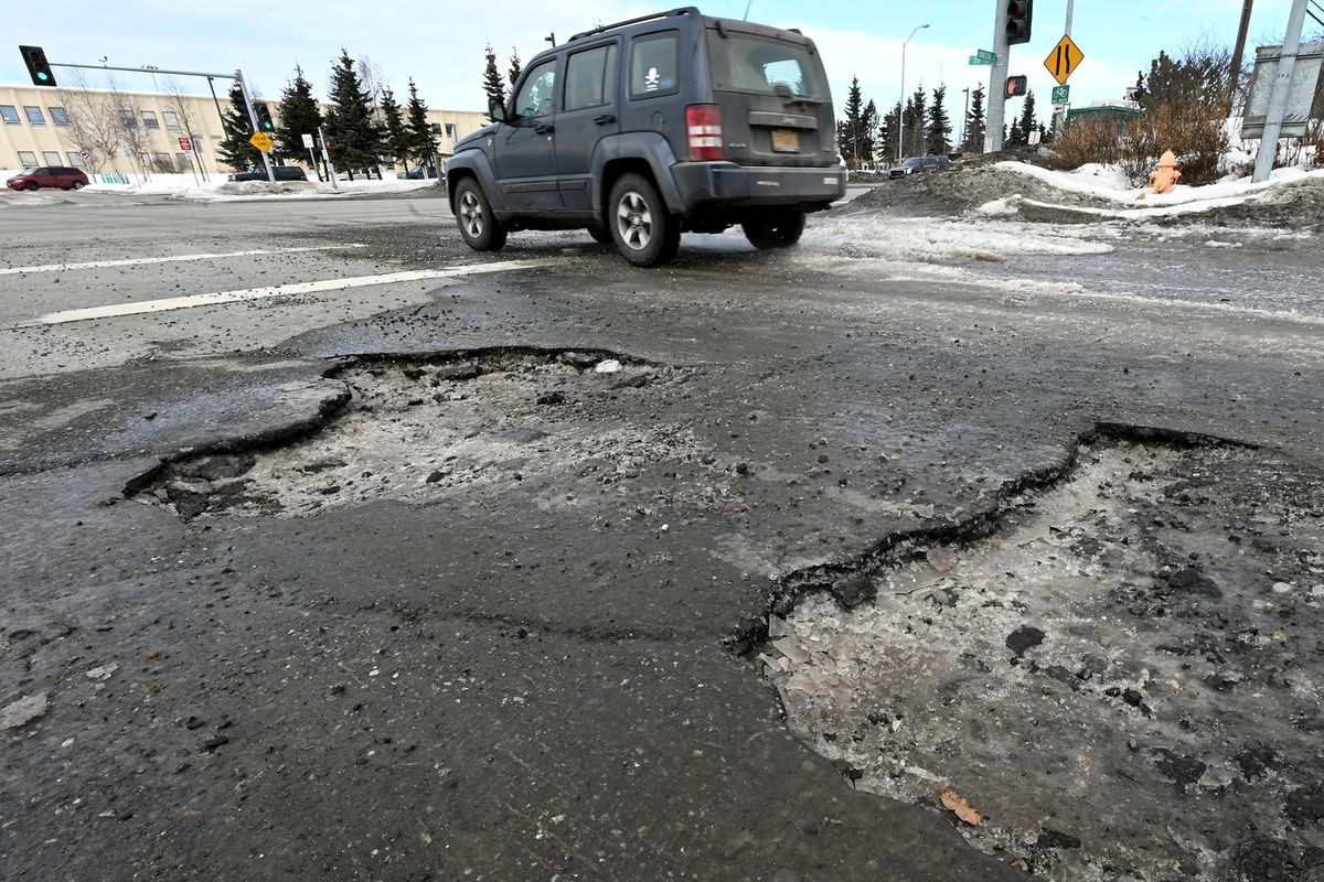 Large potholes at 26th Avenue and Minnesota Drive were getting filled by a pothole crew on Thursday, April 1, 2021. (Bill Roth / ADN)
