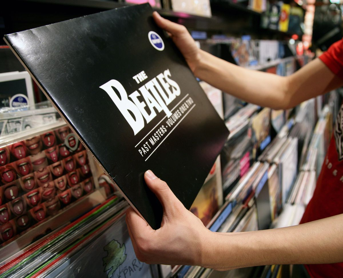 A shopper holds up a vintage Beatles album which was recorded under the Capitol Records label. Bloomberg photo by Tim Rue