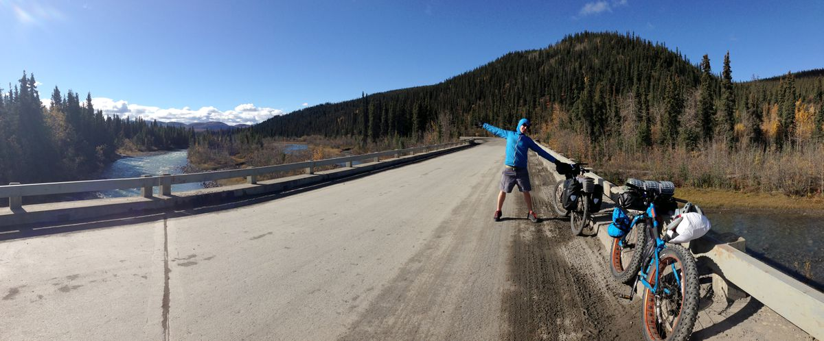 Wes Hoskins celebrates the outdoors at Sanctuary River, just past Sanctuary Campground, while cycling the Denali Park Roadin Denali National Park with the author. (Photo by Alli Harvey)