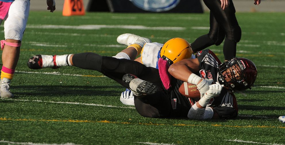 Ervin Feleti, of Barrow, brings down Houston ball carrier Kennedy Fono at Anchorage Football Stadium in Anchorage, AK on Saturday, October 19, 2019. Houston defeated Barrow 41-8 to win the Division III Alaska State Championship game. (Bob Hallinen photo)