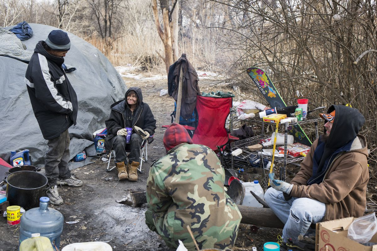 "A group of homeless people make coffee at an encampment outside of Denver on Jan. 3. Activists and homeless people are waging public campaigns and court fights against local laws that ban urban camping, as some politicians urge a ""zero tolerance"" policy. (Nick Cote/The New York Times)"