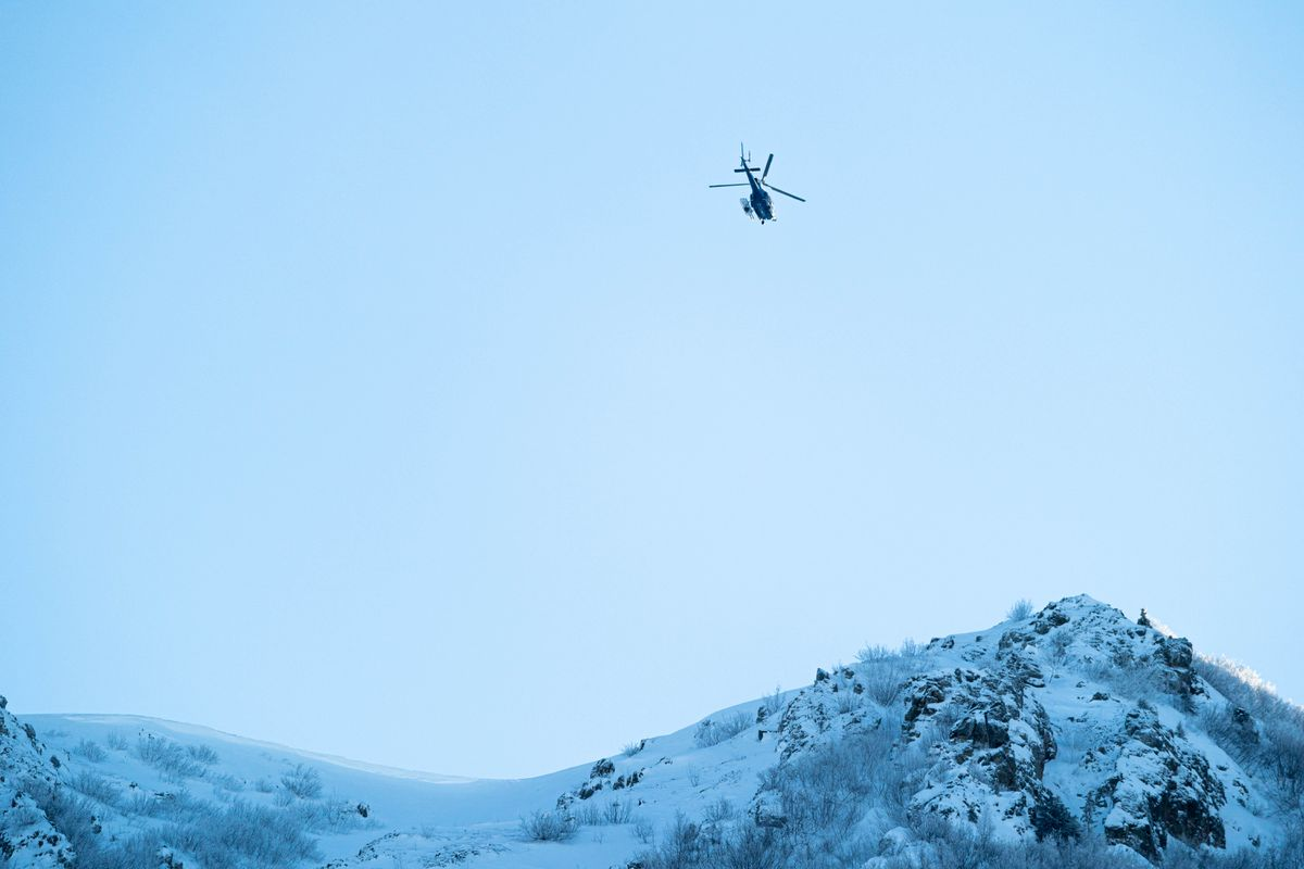 An Alaska State Troopers helicopter hovers over the Northwest Couloir of Bear Mountain on Thursday in Chugiak. AST, the Chugach National Forest Avalanche Information Center, and the Alaska Mountain Rescue Group are investigating the Tuesday avalanche that killed three hikers in the couloir. (Loren Holmes / ADN)