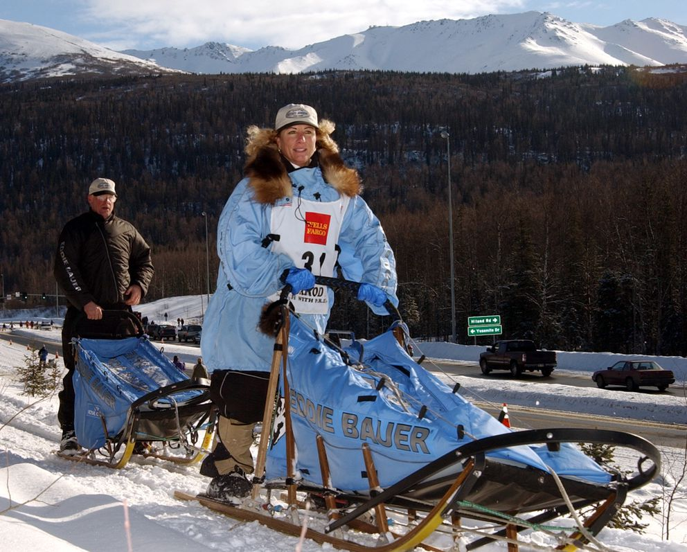 DeeDee Jonrowe crests a small rise just outside Eagle River during the ceremonial start of Iditarod 2002. (JIM LAVRAKAS / Anchorage Daily News archive)