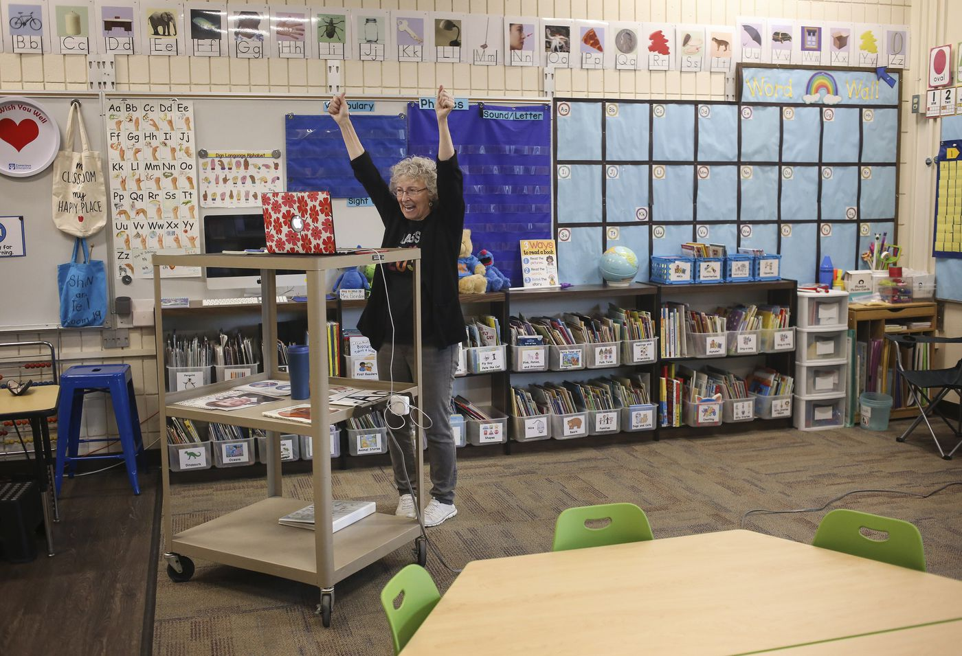 Karen Gordon celebrates the end of the first day of kindergarten as she says goodbye to her students over Zoom from her empty classroom. (Emily Mesner / ADN)