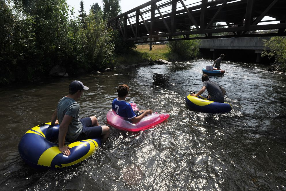 A group of tubers begin their float down Campbell Creek from Lake Otis Parkway to the Peanut Farm on Old Seward on a warm Monday, July 8, 2019. (Bill Roth / ADN)