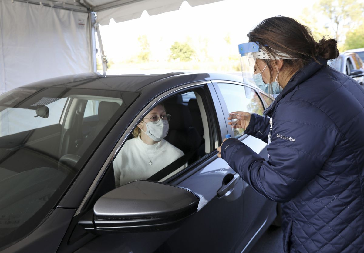 Nursing assistant Monica Brodsky, right, hands McKensie Burreson, of Madison, a funnel and vial for a saliva test that tests for COVID-19 at a drive-thru testing site in the parking lot at the UW Health Administrative Office Building in Middleton, Wis., Monday, Oct. 5, 2020. (Amber Arnold/Wisconsin State Journal via AP)