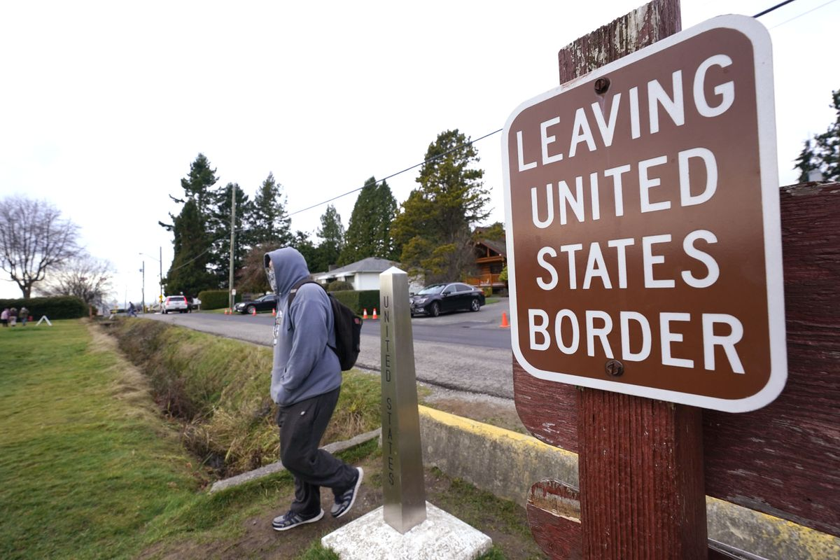 A Canadian citizen steps past a border marker and walks into the Peace Arch Historical State Park in the U.S., Sunday, Dec. 20, 2020, in Blaine, Wash. (AP Photo/Elaine Thompson)