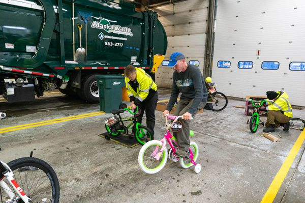 Alaska Waste driver John Clark does a wheelie to test a newly-built bicycle at Alaska Waste's bike build Saturday, Dec. 7, 2019. Alaska Waste employees donated some of the money to purchase over 70 bicycles, which will be distributed to families in need through the Salvation Army. (Loren Holmes / ADN)