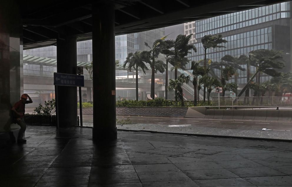 A worker, left, stands against strong wind caused by Typhoon Mangkhut in Hong Kong, Sunday, Sept. 16, 2018. Hong Kong and southern China hunkered down as strong winds and heavy rain from Typhoon Mangkhut lash the densely populated coast. The biggest storm of the year left at least 28 dead from landslides and drownings as it sliced through the northern Philippines. (AP Photo/Vincent Yu)