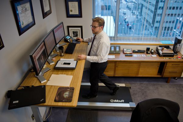 Anchorage city manager Bill Falsey walks on a treadmill while working in his office on the eighth floor of City Hall on November 30, 2017. (Marc Lester / ADN)