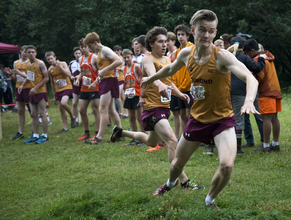 Niko Latva-Kiskola, right, is tagged by teammate Fred Rygh at a cross country relay race last month at Kincaid Park. (Marc Lester / ADN)