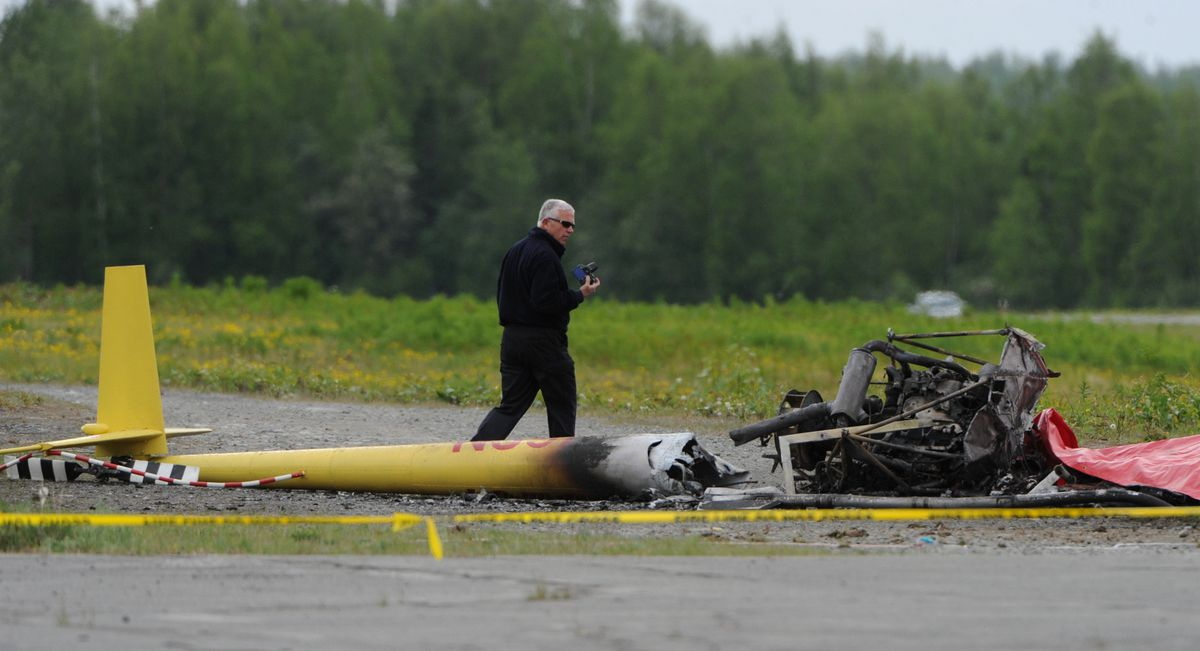 NTSB investigator Clint Johnson photographs the scene of a Robinson R44 helicopter crash that killed pilot Tom Moore, 62, of Anchorage, at Birchwood Airport on May 28, 2014. (Bill Roth / ADN archive 2014)