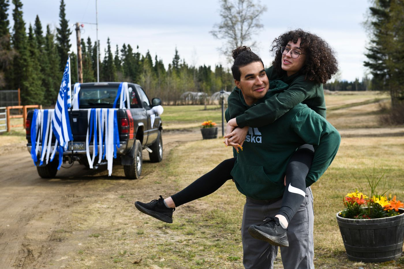 Hailey Williams jumps up on the back of her older brother Cameron after they decorated his pickup truck for the graduate car parade. (Marc Lester / ADN)