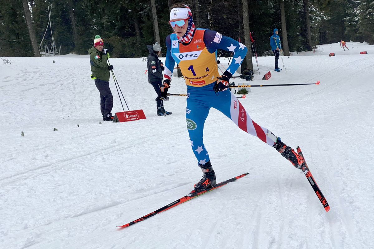 Gus Schumacher carries an American flag to the finish line of the men's relay race at the World Junior Championships earlier this year in Germany. (Photo by Jim Jager)